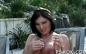 Alluring babe with huge bust positions for a difficulty camera while smoking